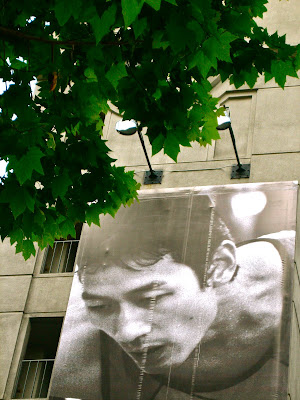 photo of a billboard in San Francisco with the image of a man looking down, and there are green leaves above the billboard