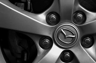 A black and white image of a wheel of a Mazda