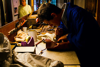A Leather craftsman engraves a handbag - Firenze, Italy