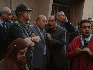 المحافظ عادل لبيب يستمع لشرح بينما يقف في موقع العمارة المنهارة بلوران
