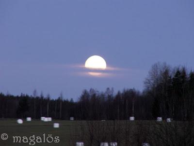 Månen på väg ner mellan molnen