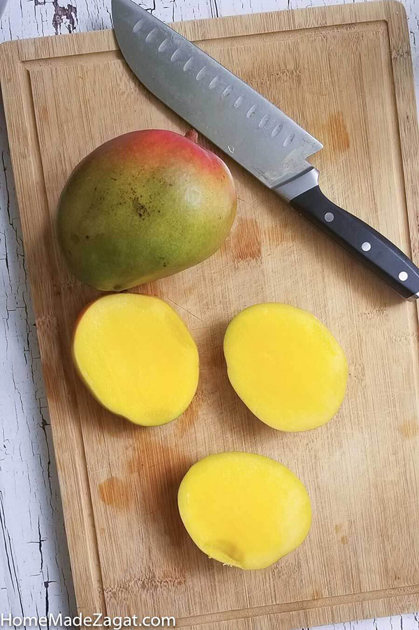 Mango sliced with cheeks off showing pulp of mango
