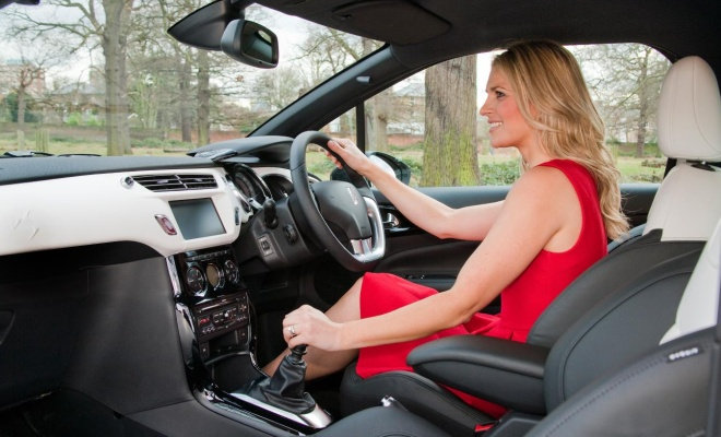 Citroen DS3 being driven by a young blonde woman in a red dress