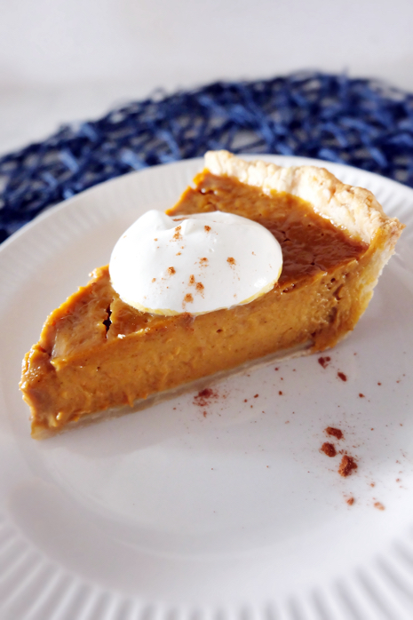 slice of pumpkin pie on plate with whipped cream