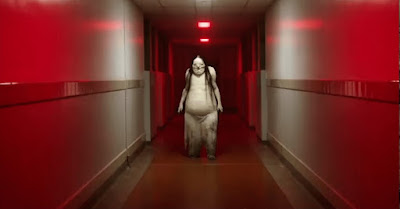 Movie still for the 2019 horror thriller Scary Stories to Tell in the Dark where The Pale Lady walks down a red hallway toward Austin Zajur