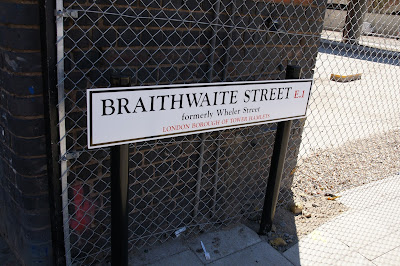 Photograph of a street sign in front of a wire fence. The modern sign is white, with black text saying 'BRAITHWAITE STREET E1 formerly Wheler Street, LONDON BOROUGH OF TOWER HAMLETS'