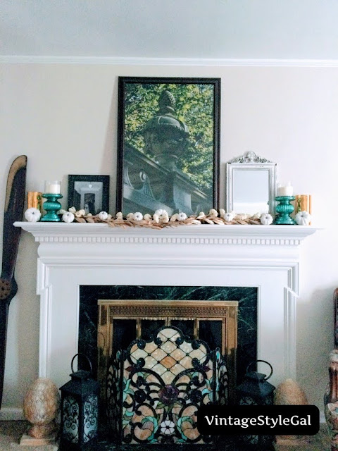 Final mantel presentation with teal candlesticks, candles, white pumpkins, large photo of urn, mirror, and wedding picture of couple