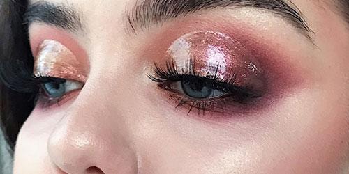Ojos azules maquillados con gloss de labios y tonos rosas