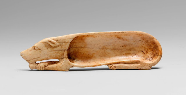 An Egyptian cosmetic holder in the shape of a dog; pets in art
