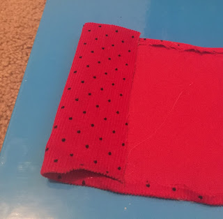 A picture of a piece of red fabric being folded into a bow