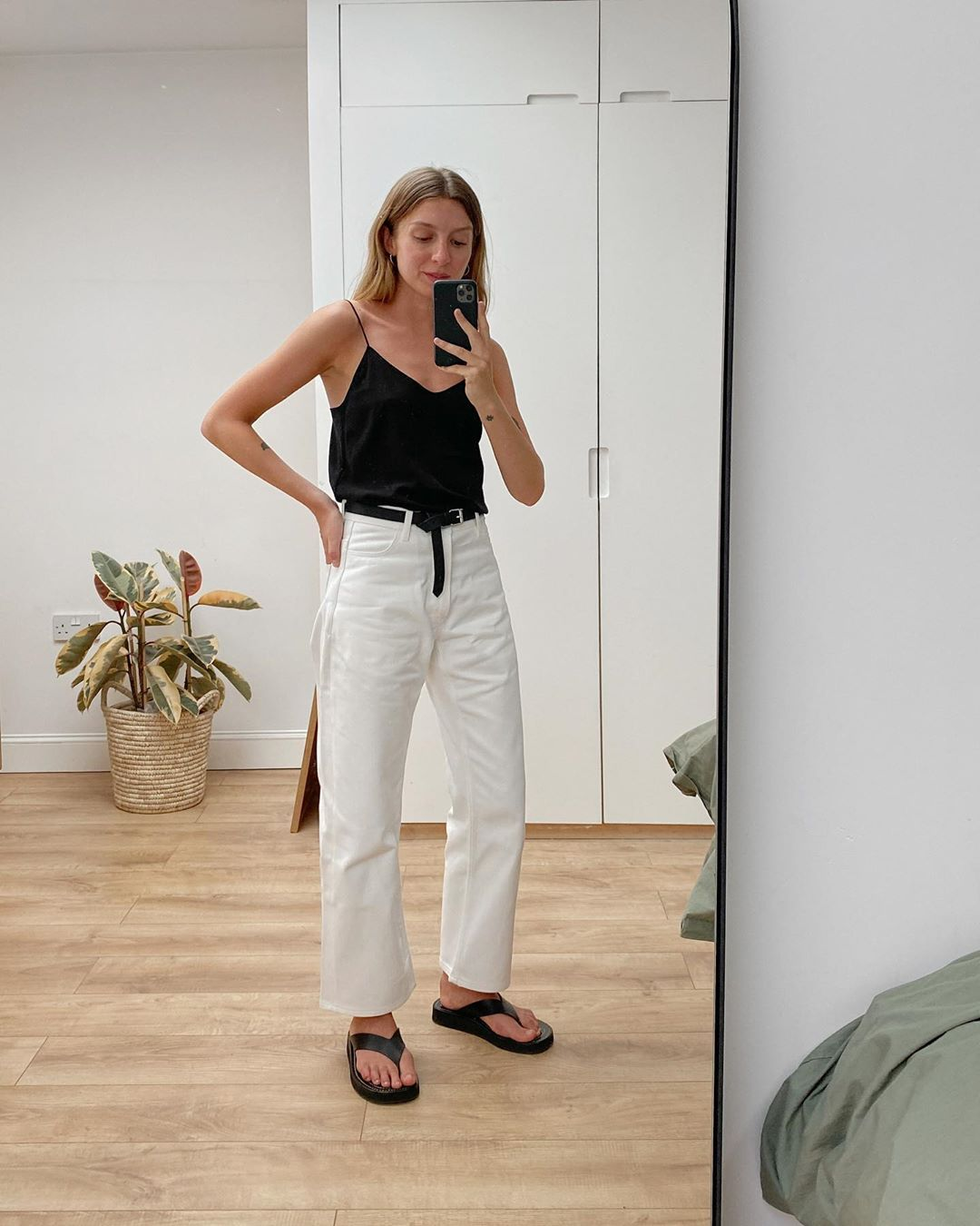 Casual-Chic Outfit Idea — Brittany Bathgate in a black cami, white jeans, and black flip-flops