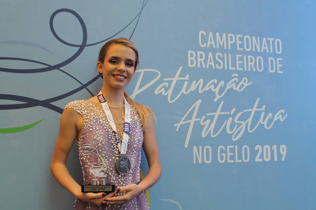 """Isadora Williams posa para foto segurando troféu. No letreiro está escrito """"Brasileiro de Patinação artística no gelo 2019"""""""