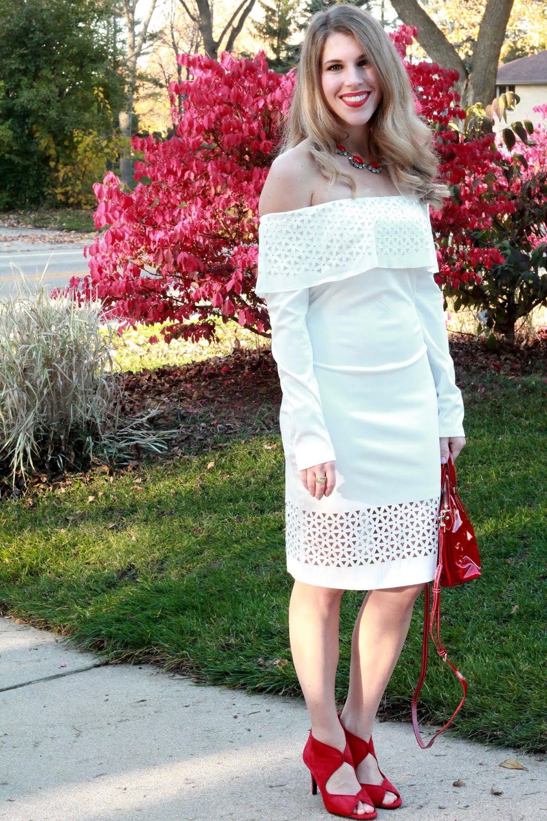 white laser cutout off shoulder white dress, red heels, red Dooney & Bourke bag, red statement necklace