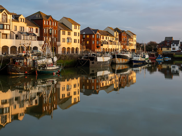 Photo of reflections on the calm water in Maryport Harbour