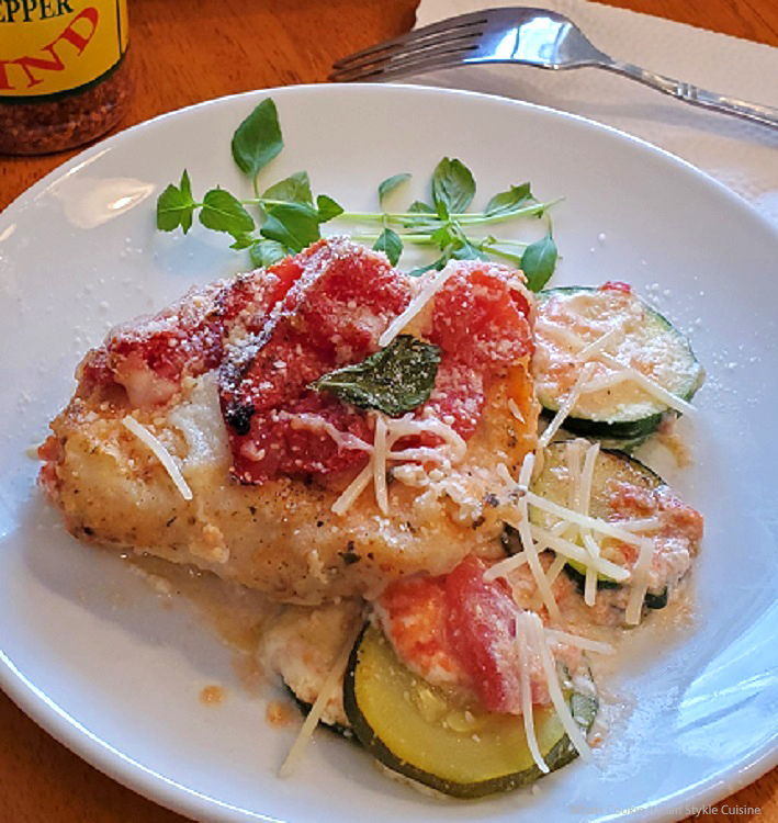 chicken topped with tomato, zucchini, cheese and ricotta