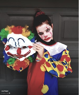 Picture of a young girl dressed up as a terrifying clown for Halloween. What does Halloween Have To Do With Swimming?