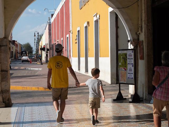 Padre e hijo de espaldas paseando de la mano bajo unos arcos