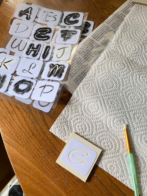 Photo of wooden squares being stenciled