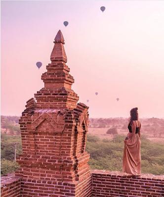 Monument Birman avec une fille contemplant le levé de soleil et les mogolfières au loin