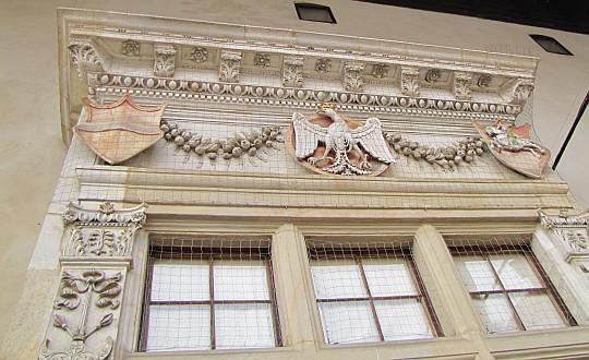 Zamek Królewski na Wawelu. Zamkowe okna ujęte kamiennymi zdobieniami.