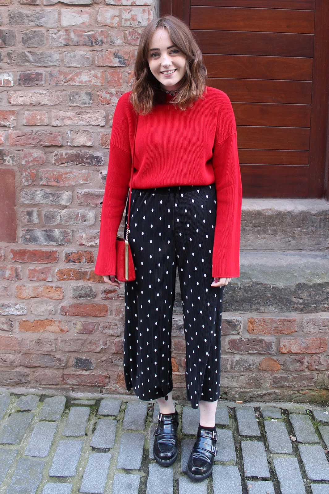 red oversized sleeve jumper, polka dot pleated trousers, monk shoes