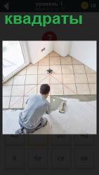 мужчина укладывает квадратные плитки на полу