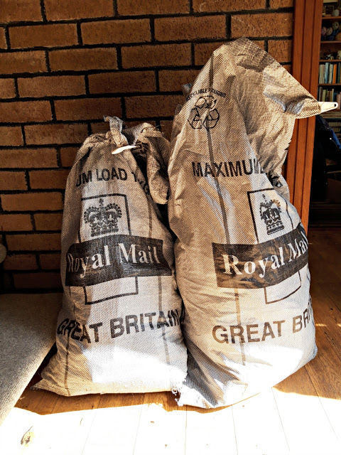 Two grey Royal Mail bags full of sock parcels sitting on a wooden floor next to grey carpeted stairs and leaning against a decorative brick internal wall