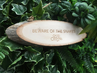 photo of a wooden sign against green foliage, reading 'beware of the snakes'
