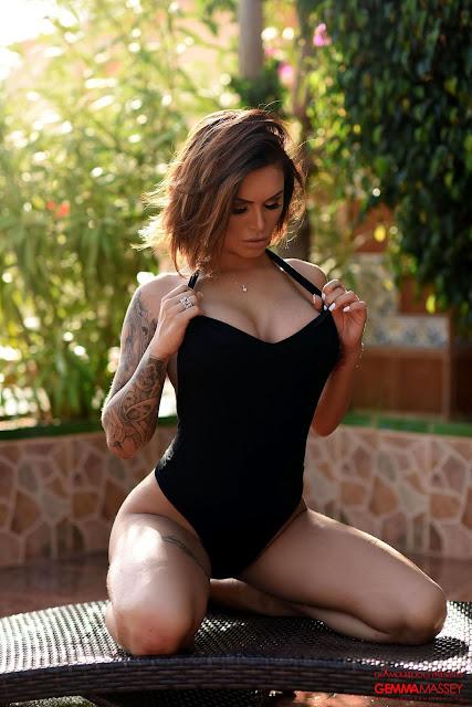 Gemma Massey looking at her sexy boobs black bodysuit