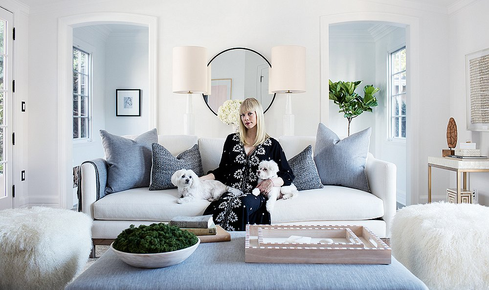 Inteiror design ideas for modern farmhouse living rooms. Erin Fetherston in her white living room with her maltese dogs.