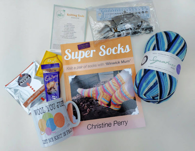 An orange book on a cream background surrounded by a mug, tea and coffee bags, a pack of knitting accessories, a purple pin badge and a ball of blue and white striped yarn