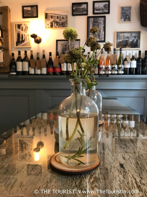 Wine bottles, framed photographs on a wall, a table with a glas top in a dimly lit room.