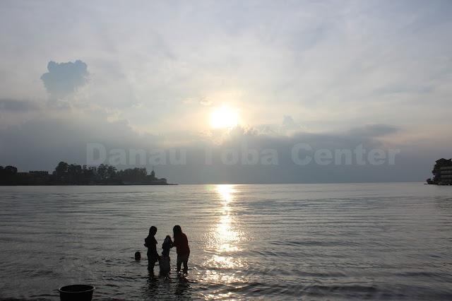 Dua orang remaja menyuci pakaian dengan latarbelakang terbenamnya matahari di lokasi pelabuhan Danau Toba Parapat