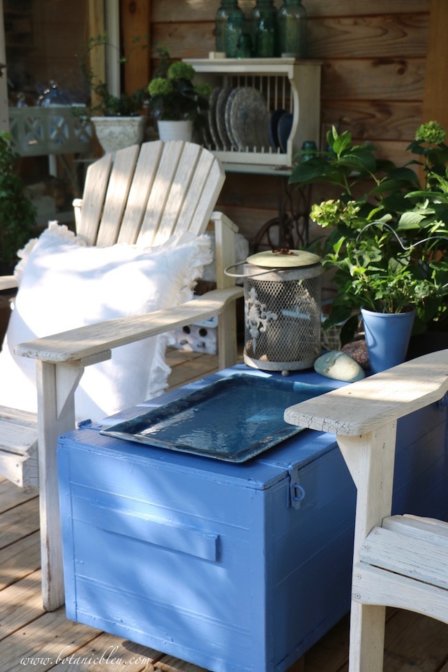 Fresh blue exterior paint protects a rustic trunk used as a coffee table on a back porch