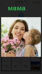 дочка целует маму в щеку с букетом цветов