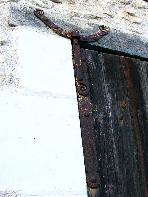 Blacksmith made hinge on a barn door.  Indre et Loire, France. Photographed by Susan Walter. Tour the Loire Valley with a classic car and a private guide.
