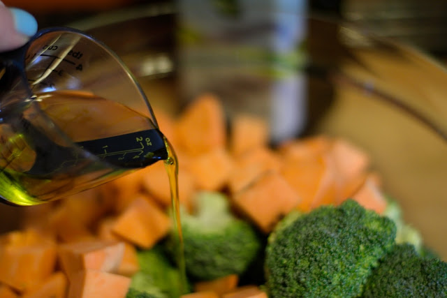 Extra Virgin Olive Oil being added to the bowl of prepped broccoli and sweet potatoes.