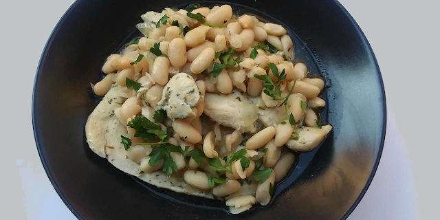 Chicken and white bean broth with parsley in black bowl