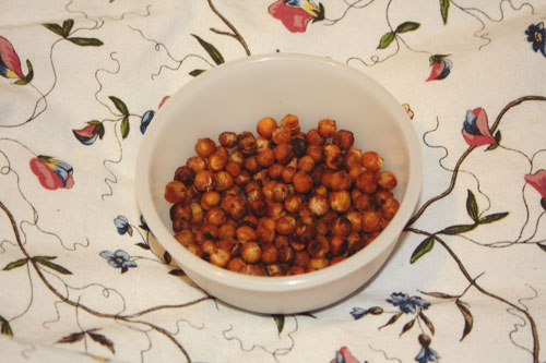 Spicy Roasted Chickpeas in a tupperware bowl, on an IKEA duvet