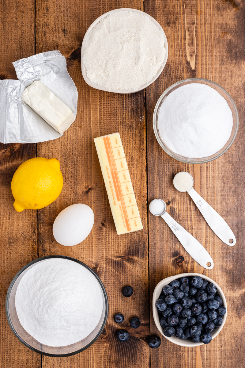 Overhead photo of the ingredients needed to make Keto Blueberry Cheesecake Cookies on a wooden table.