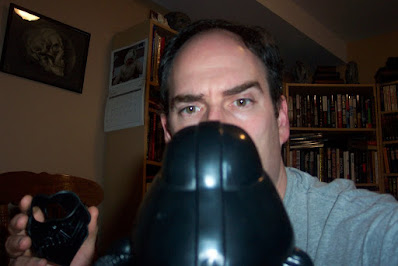 Picture of a man unmasking a Darth Tater doll