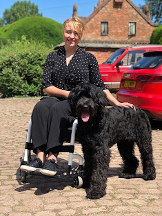 A woman with blond hair sat in a wheelchair with a black labradoodle dog sat beside her.