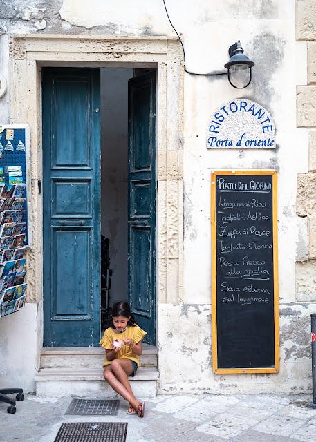 Niña con camisa amarilla sentada en una puerta azul comiendo un helado