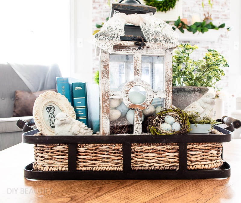Spring tray with blue books, stone birds and lantern filled with eggs