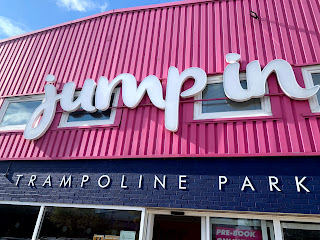 Sign in front of a building reads Jump In trampoline park