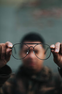 a blurry picture of a man holding his glasses away from his face