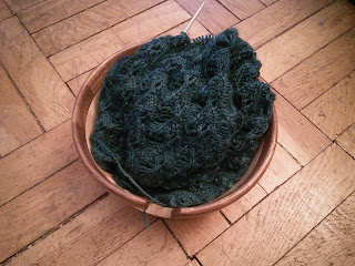 A deep turquoise fingering-weight lace cowl on a circular needle.  Yarn and cowl are tucked inside a wooden yarn bowl.