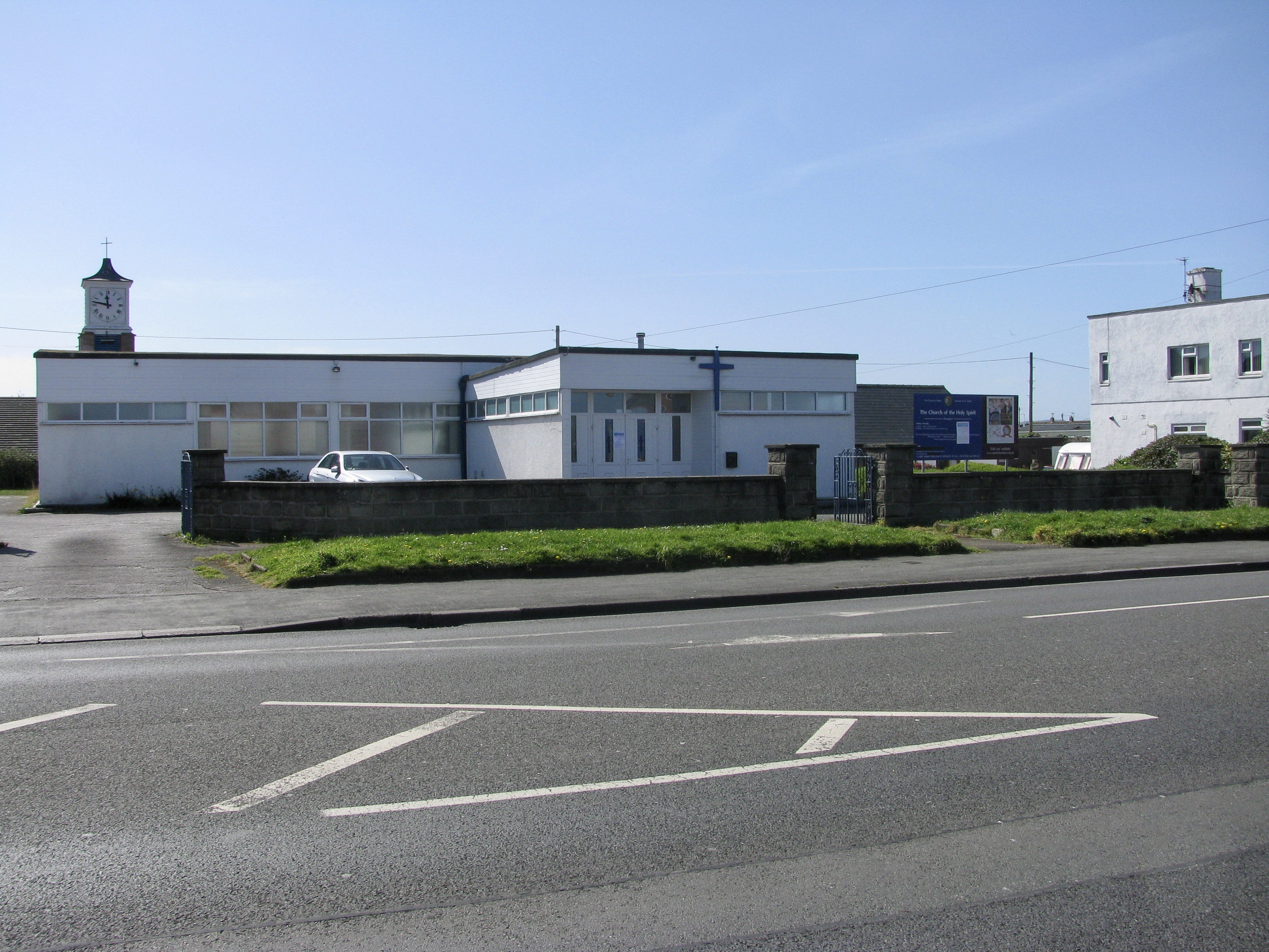 Photo of Church of the Holy Spirit, Taken on a sunny day. Modern White, flat roof building with car parking.