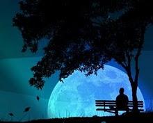 Άντρας που κάθεται σε παγκάκι ατενίζει τη σελήνη.