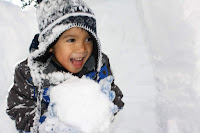 young boy in a beanie and ski jacket holding a giant snow ball. His mouth is open with excitement and a smile